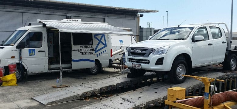 Isuzu DMax on Brisbane City Council DT80 Test dynamometer beside mobile testing laboratory and associated equipment.