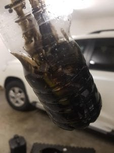 Bottle with excess sludge removed from engine after using Flushing Oil Concentrate