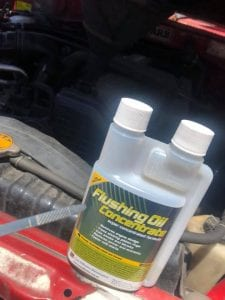 Clean diesel engine dipstick with a bottle of flushing oil concentrate