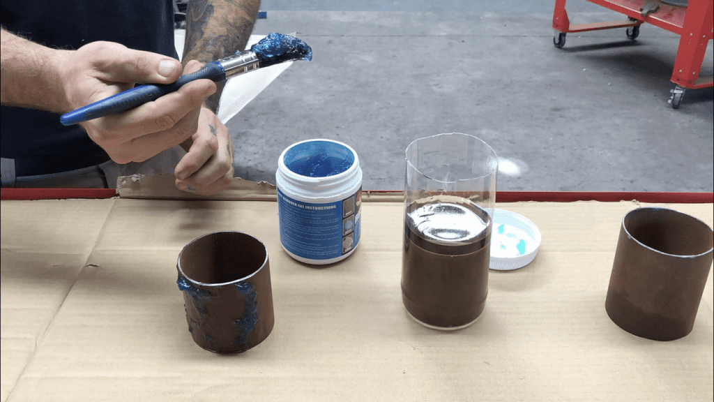Applying  rust remover gel to a steel pipe